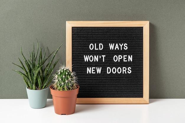 古い方法は新しい扉を開かないでしょう。レターボード、サボテン、白いテーブルの上のジューシーな花の動機付けの引用。その日のコンセプトの心に強く訴える引用。正面図。
