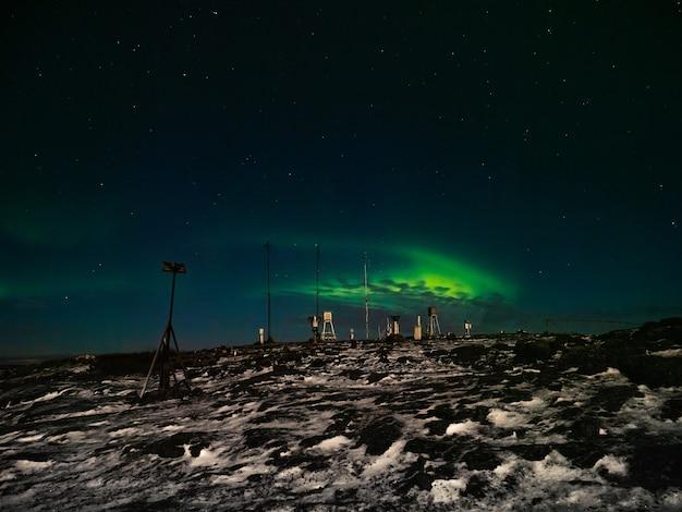 오래된 기상 관측소. 오로라 보 리 얼리 스와 밤 겨울 극지 풍경. 러시아.