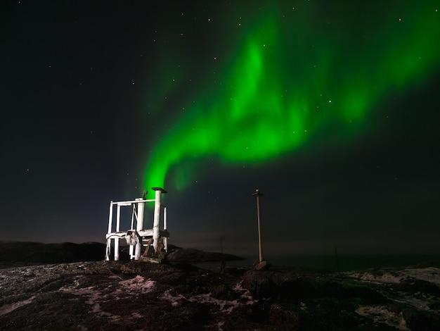 Old weather station. winter teriberka. evening polar landscape with the aurora borealis.