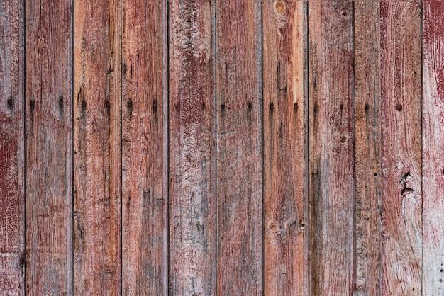 線やひび割れのある古くて風化した老朽化した木製ドア