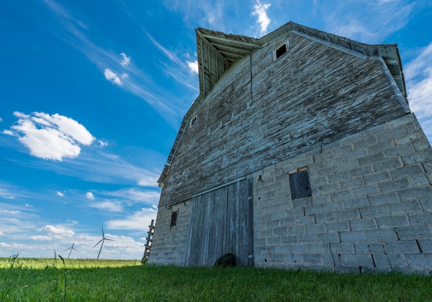 Old weathered barn on the prairies with wind turbines