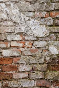 古い風化したレンガの壁。ひびの入った漆喰の背景を持つ古いレンガの壁