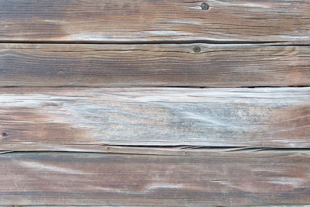 Old weathered brown and white wood surface with long boards lined up.