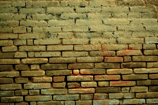 Old weathered clay brick  texture with eroded masonry exposing the bricks in a full frame view.