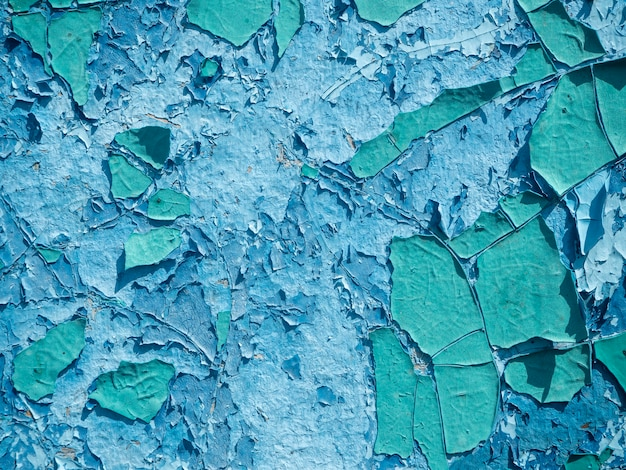 The old weathered peeling paint is blue on the wall. close-up, background, texture