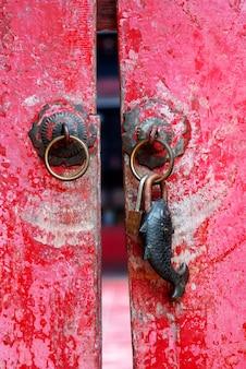 Старый выдержанный красный покрашенный традиционный стиль деревянной двери китайский с петлей ручки металла и сформированным рыбами ржавым кольцом для ключей металла.