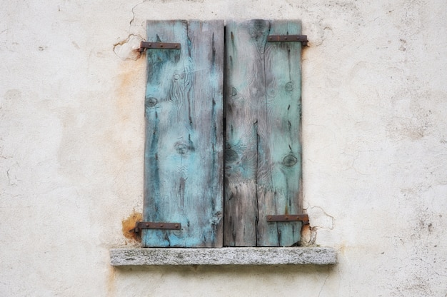Old weathered wall with blue rusty wooden shutters