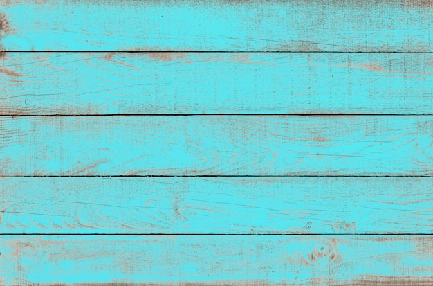 Old weathered wooden plank painted in turquoise blue color.
