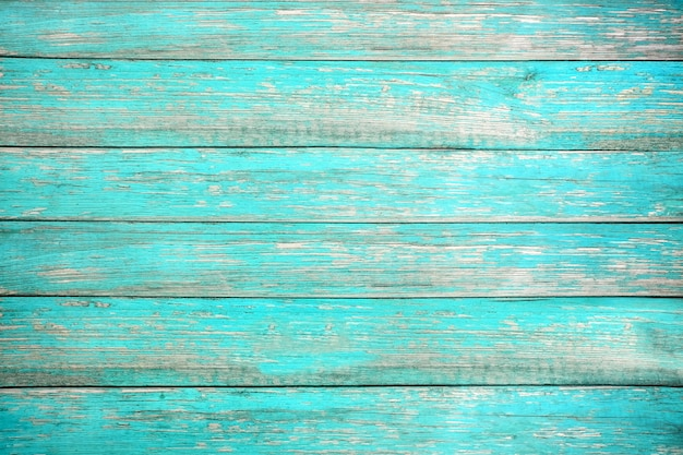 Old weathered wooden plank painted in turquoise or blue sea color.