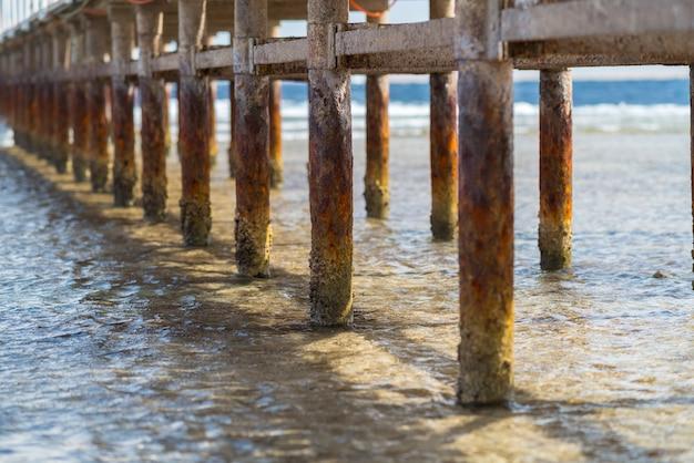 오래 된 열 대 섬의 해변가에 얕은 바닷물과 부두에 나무 기둥을 풍 화
