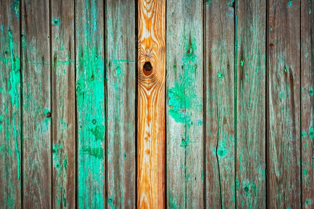 Old and weathered wooden wall background, with peeled green paint and rusty nails and single new yellow stained plank.