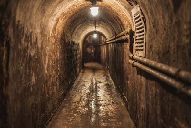 Old wet long narrow dark underground tunnel with dim lighting