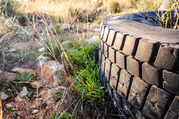 Old wheels of unrecycled cars thrown in a natural field pollute the earth.