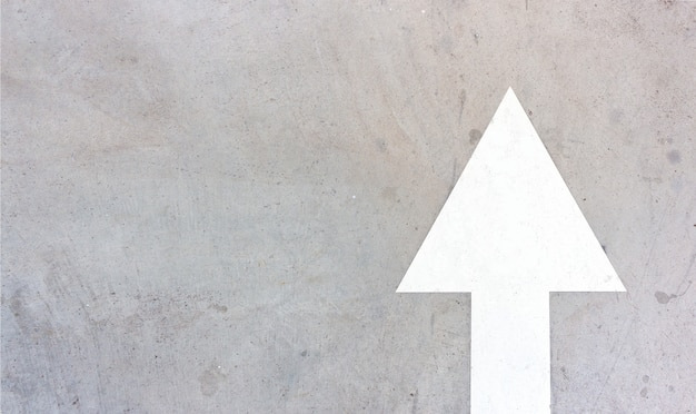 Old white arrow on the cement road background