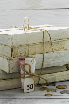 Vecchi libri bianchi con soldi e monete sulla parete di legno