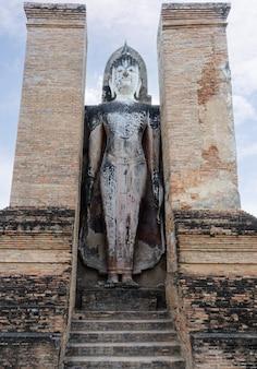 Старая белая статуя будды стоит в старинной церкви, которая находится в историческом парке.