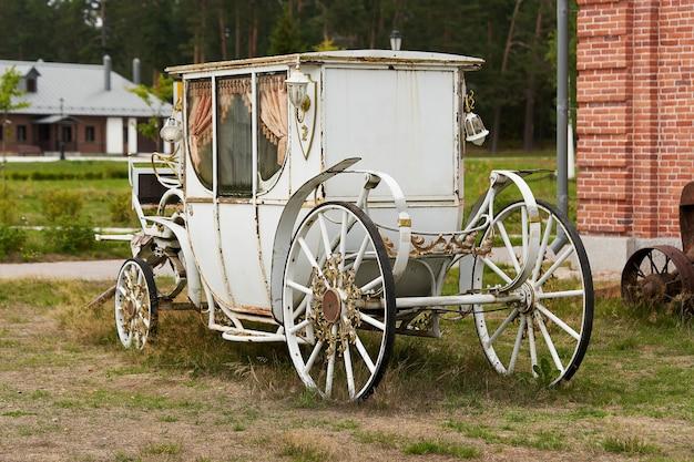 Старый белый вагон на фоне здания из красного кирпича. белая старинная карета