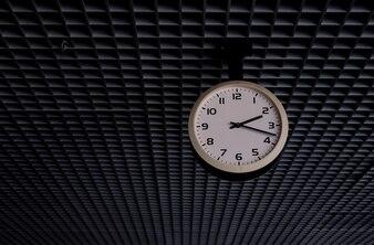 Старые белые круглые часы, висящие под потолком.