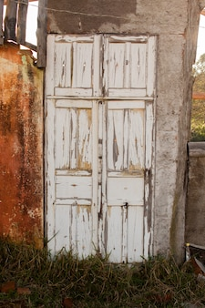 Old white colored door in abandoned house in countryside
