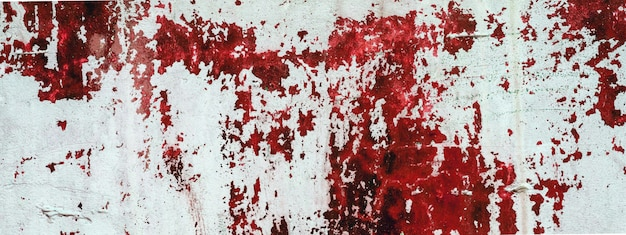 Old white concrete wall stained with red paint