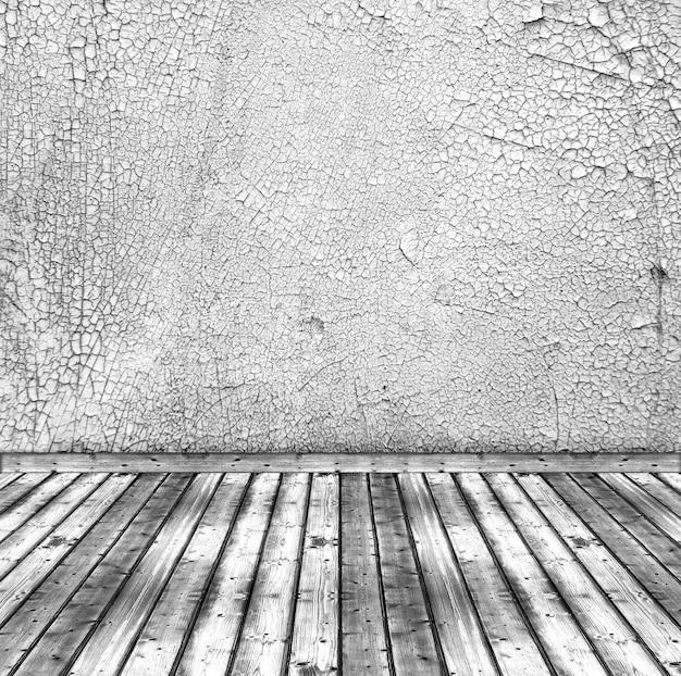 오래 된 흰색 금이 간 벽과 나무 바닥입니다. 소박한 인테리어 배경