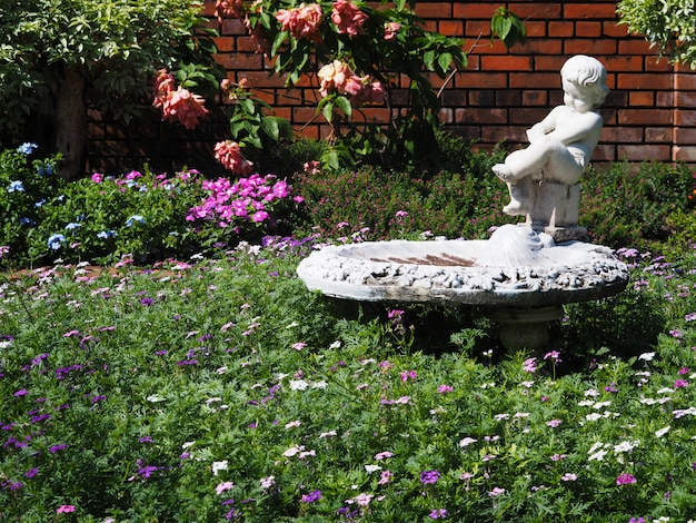 Old white sculpture and flowers in the park.