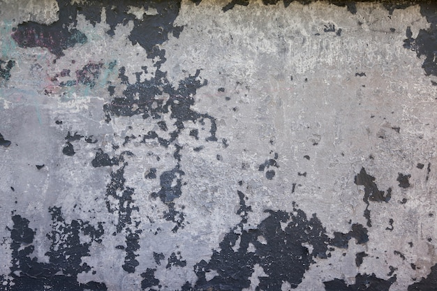 An old white stucco wall with cracked painted surface of horizontal blank grunge background