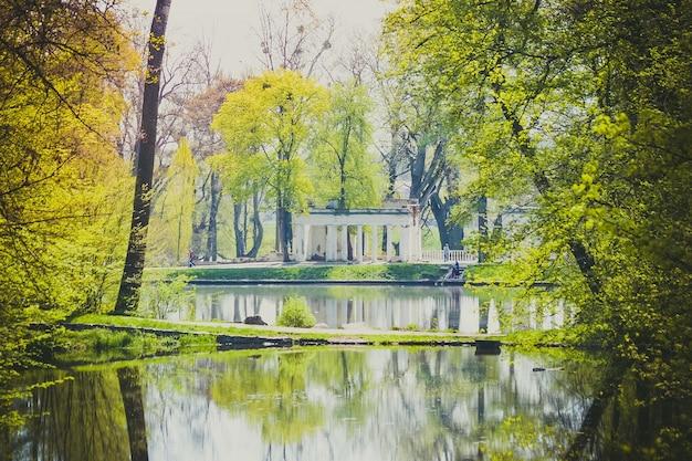 봄에 호수가 있는 공원의 오래된 흰색 탑 유적