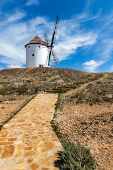 Old white windmills, made of stone, on the field with blue sky and white clouds. la mancha, castilla, spain. europe,