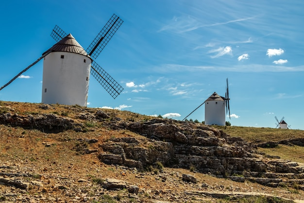 Old white windmills, made of stone, on the field with blue sky and white clouds. la mancha, castilla, spain. europe.