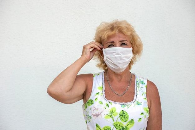 Старая белая женщина в летнем платье надевает белую медицинскую маску на белом