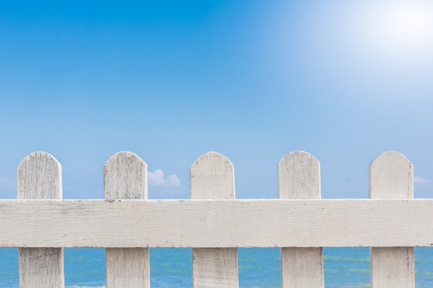 Old white wooden fence on a blue sky