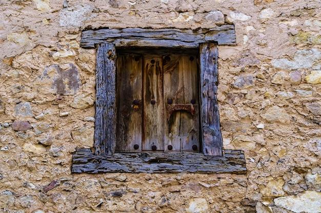 木とヴィンテージの素材で作られた石造りの家の古い窓。スペイン、ペドラサ。