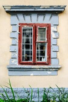 격자와 오래 된 창입니다. 창문 뒤에 종교 인형이 있습니다. 프레임과 벽에 페인트가 벗겨집니다.