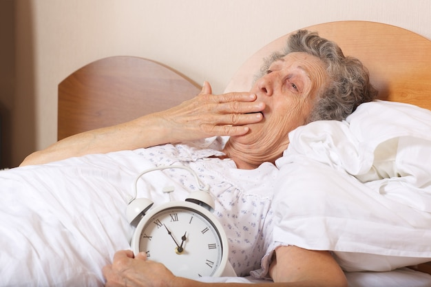 Old woman between 70 and 80 years old is yawning with vintage alarm clock