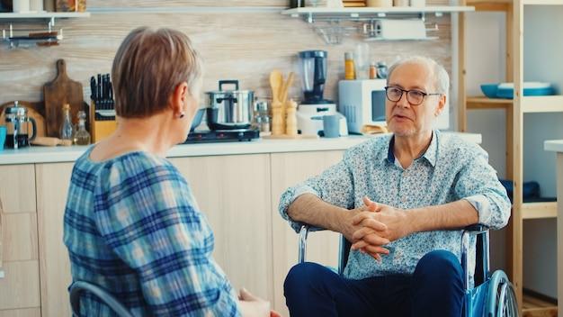 キッチンでおしゃべりをしている車椅子の老婆と障害のある夫。キッチンで夫と会話をしている高齢者。歩行障害のある障害者との生活