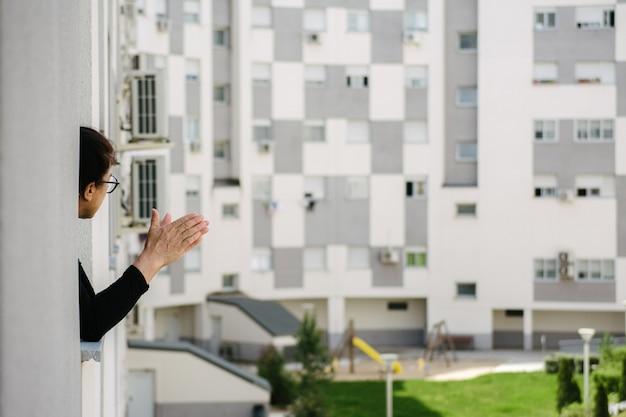Старуха аплодирует людям, борющимся с коронавирусом (covid19), из окна на закате в своем сообществе соседей