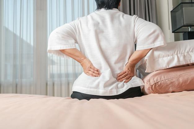 Старая женщина боли в спине дома, концепция проблемы со здоровьем
