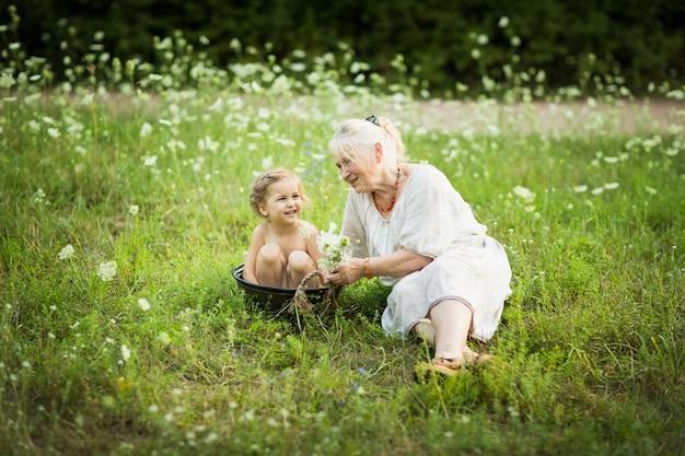 老婆は花の周りの夏の日に屋外の盆地で小さな女の子をお風呂に入れます