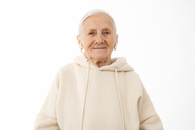 Old woman in beige hoodie with white airpods in ears