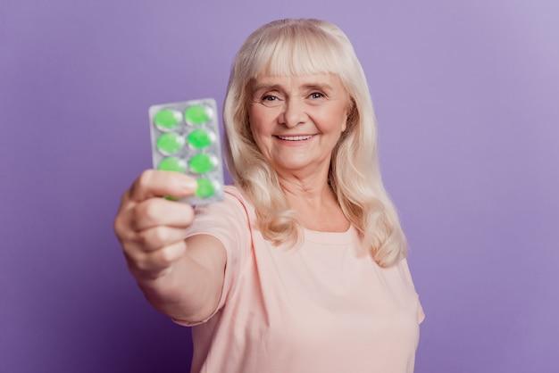 늙은 여자는 보라색 배경 위에 손에 효과적인 의료 정제를 보여줍니다