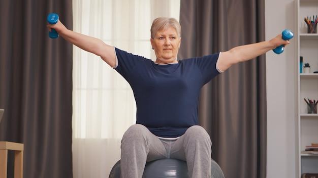 リビングルームでフィットネスボールで運動している老婆。ウエイトダンベル活動で自宅でトレーニング健康的なライフスタイルスポーツフィットネストレーニングを持ち上げる老婆