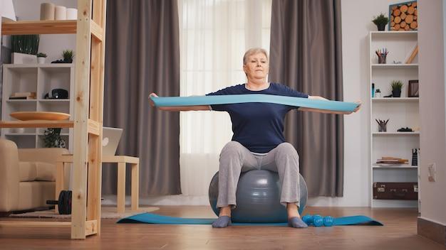 フィットネスボールに座って抵抗バンドで運動している老婆。ウエイトダンベル活動で自宅でトレーニング健康的なライフスタイルスポーツフィットネストレーニングを持ち上げる老婆