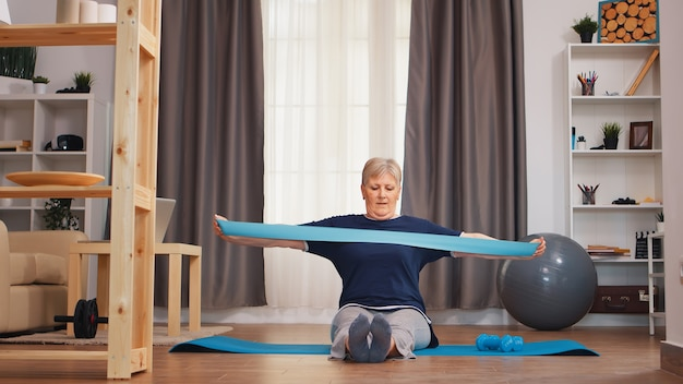 ヨガマットの上に座って抵抗バンドで運動している老婆。年金受給者の老婆は、退職時に健康的なライフスタイルを生きるフィットネスを伸ばし、自宅での運動を訓練します
