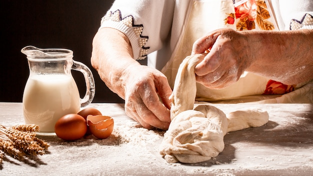 Old woman, grandmother hands with flour splash. cooking bread slams ball dough on white powder covered table. concept of nature, food, diet and bio. menu recipe place for text