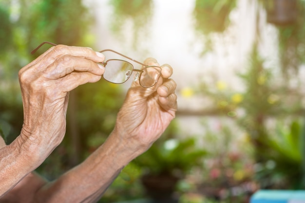 Old woman hand hold with eyeglasses. senior people health care