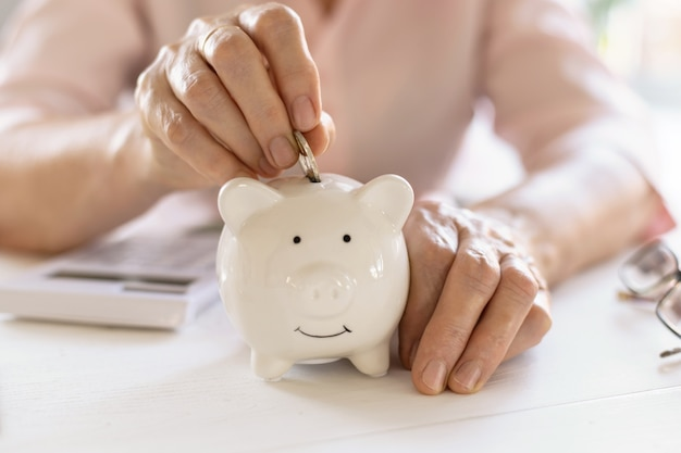 Old woman hands put money coins in a piggy