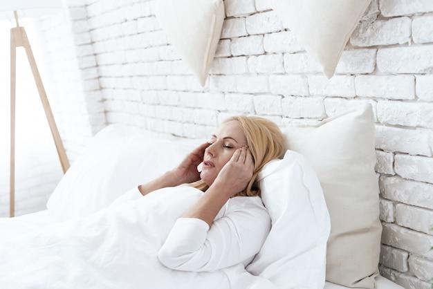 歳の女性がベッドで横になっている頭痛があります。