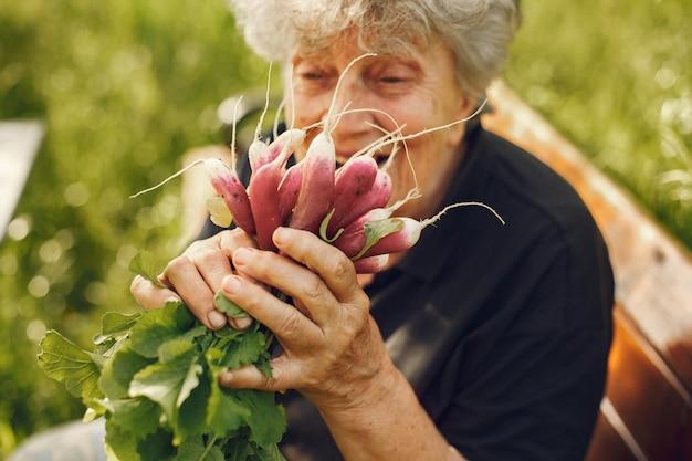 Vecchia donna in un cappello che tiene ravanelli freschi