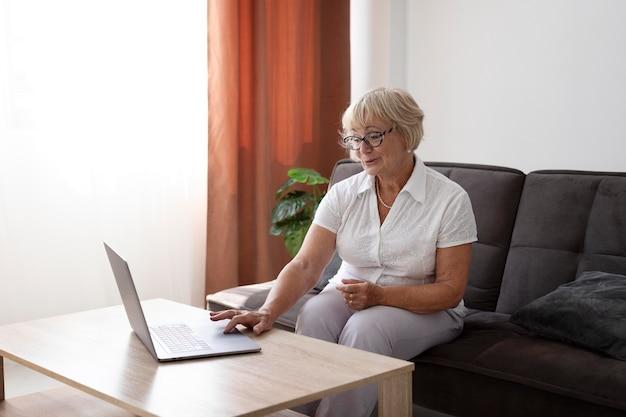 Пожилая женщина разговаривает по видеосвязи со своей семьей
